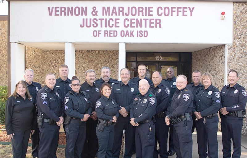 group shot of the police department standing in front of Coffey Justice Center
