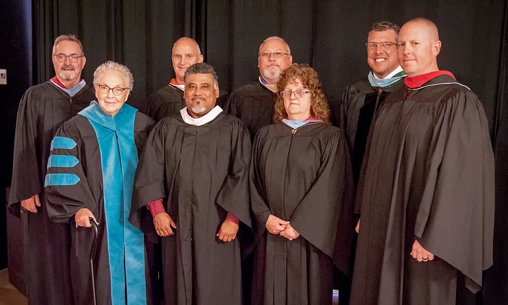 board members and superintendent in graduation gowns
