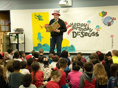 Administrator reading to students while wearing Dr. Seuss hat