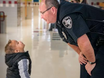 Officer talking to young kindergarten student