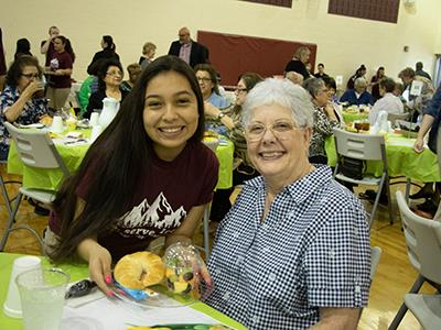 Student serving lunch to senior citizen