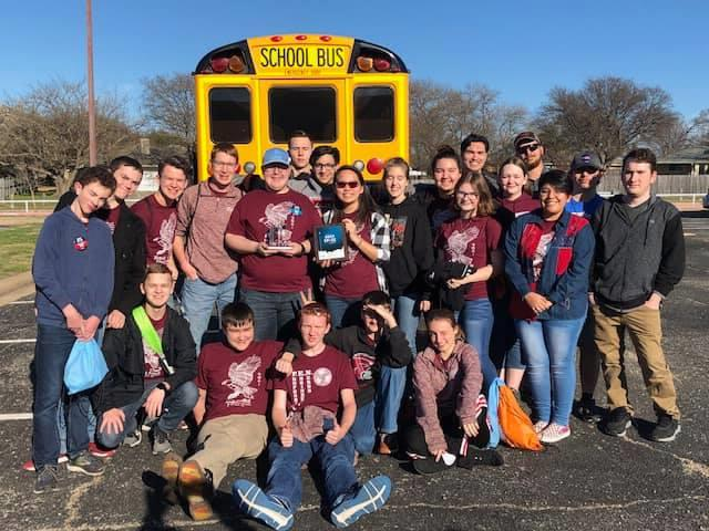 Robotics team posing in front of bus holding their trophies
