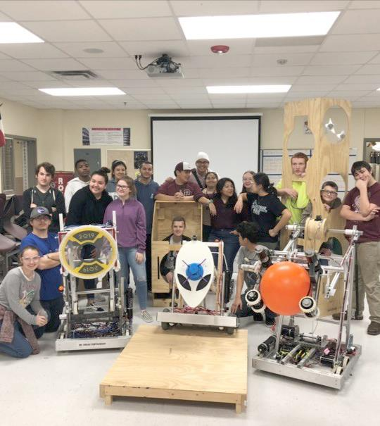 robotics teams posing with their robots that they built