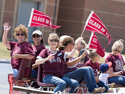 Alumni riding a float in homecoming parade